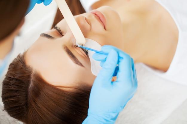 Jonge vrouw in een schoonheidsstudio op een procedure van de wimperuitbreiding