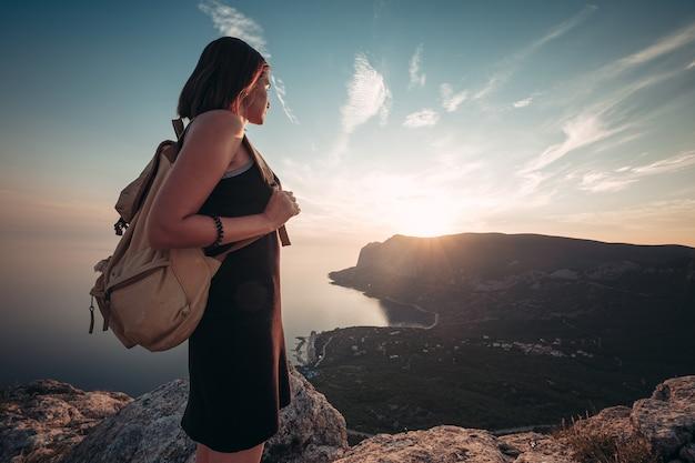 Jonge vrouw in een sportjurk met rugzak geniet van het uitzicht op de bergen en de zee bij zonsondergang. reizen en actieve levensstijl concept. glamping