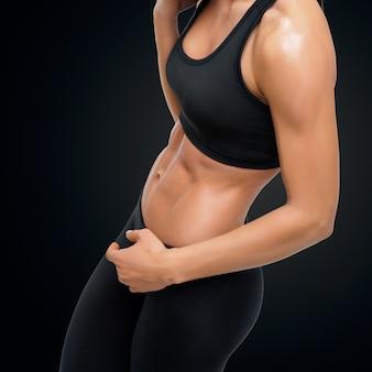 Jonge vrouw in een sportschool met haar goed getrainde lichaam