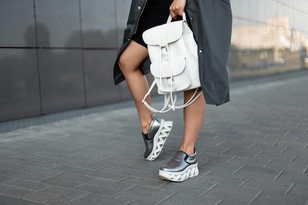 Jonge vrouw in een stijlvolle lange jas in trendy moderne sneakers met een stijlvolle witte lederen rugzak staat op straat. close-up van vrouwelijke benen en rugzak.