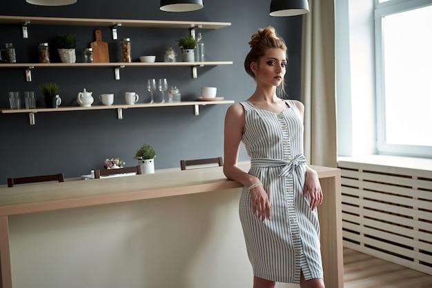 Jonge vrouw in een stijlvolle witte jurk poseren in de keuken.