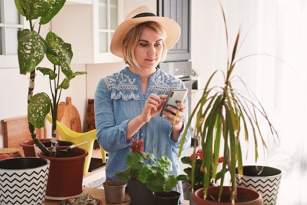 Jonge vrouw in een strohoed die huisbloemen groeit en plant die informatie in een smartphone lezen