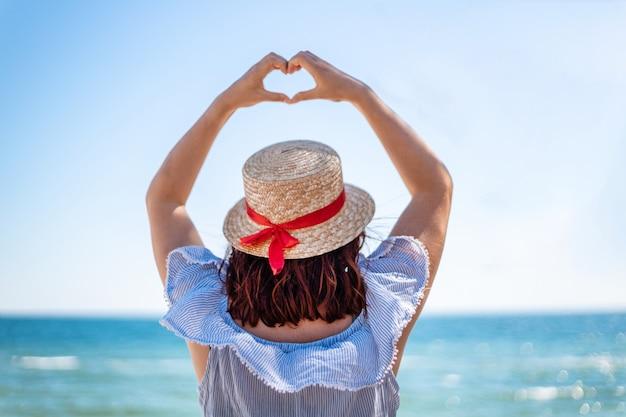 Jonge vrouw in een strooien hoed en een zomerjurk rug uitzicht maakt liefde teken met haar handen op blauwe zee