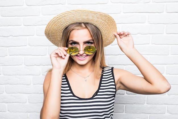 Jonge vrouw in een strooien hoed en zonnebril staat in de buurt van een witte bakstenen muur