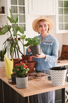Jonge vrouw in een strooien hoed houdt zich bezig met de teelt en het planten van huisbloemen