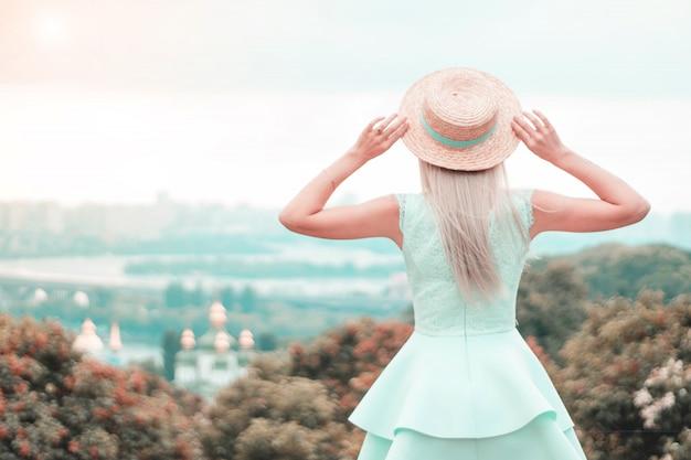 Jonge vrouw in een strooien hoed kijkt in de verte