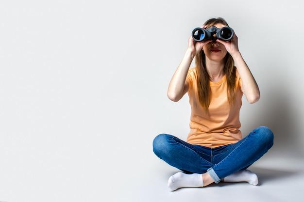 Jonge vrouw in een t-shirt en spijkerbroek zittend op de vloer kijkt door een verrekijker op een lichte achtergrond