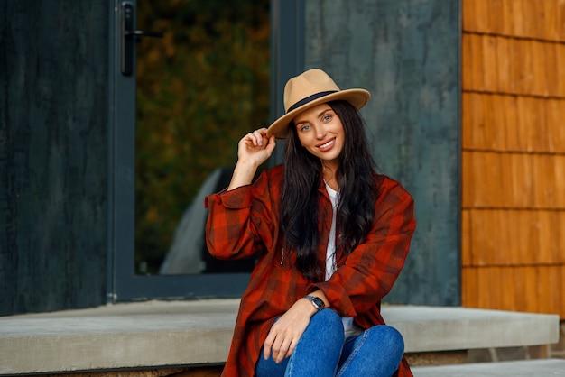 Jonge vrouw in een trendy rood shirt bruine hoed en denim broek zit op een trap, in de buurt van haar eigen huis.