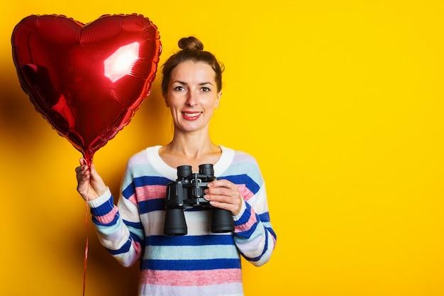 Jonge vrouw in een trui houdt het hart van een luchtballon en kijkt door een verrekijker op een gele achtergrond. valentijnsdag samenstelling.
