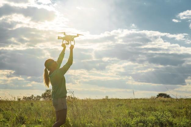 Jonge vrouw in een veld lanceert de drone in de lucht