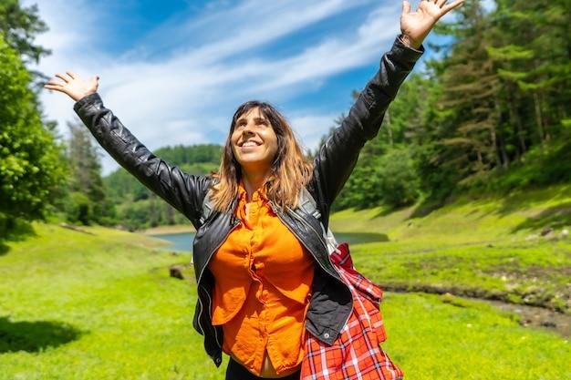 Jonge vrouw in een veld met een meer en een dennenbos