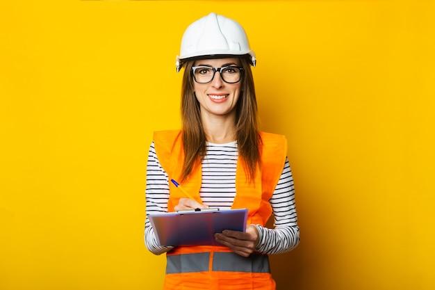 Jonge vrouw in een vest en helm houdt een klembord op een gele achtergrond. bouwconcept, nieuwbouw. banier.