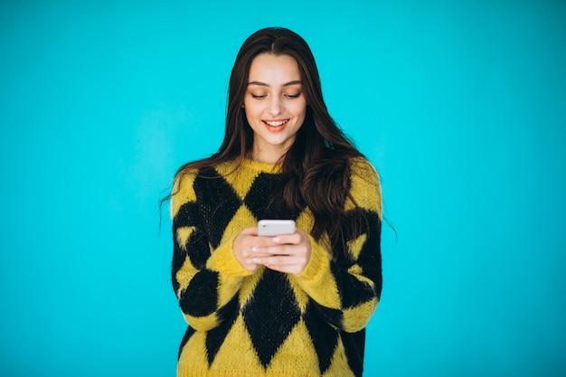 Jonge vrouw in een warme trui met behulp van de telefoon