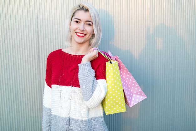 Jonge vrouw in een winkelcentrum terwijl u op zoek naar camera