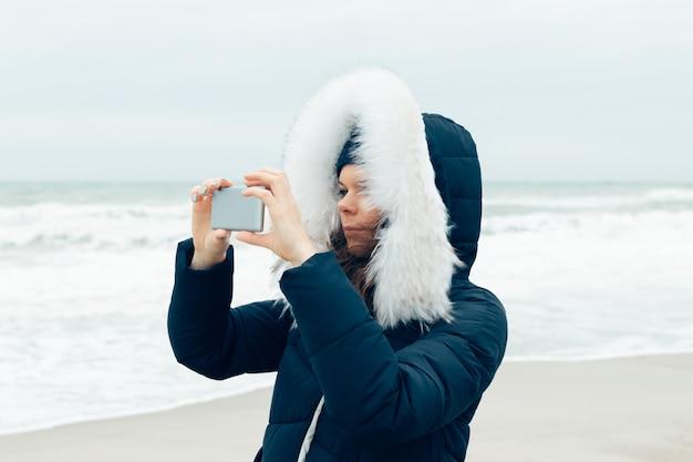 Jonge vrouw in een winterjas met een kap die een mobiele telefoon op het strand met behulp van