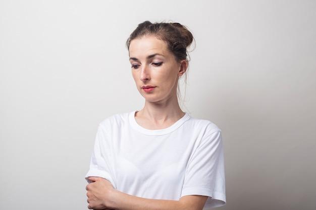 Jonge vrouw in een wit overhemd kijkt naar de bodem op een lichte achtergrond.