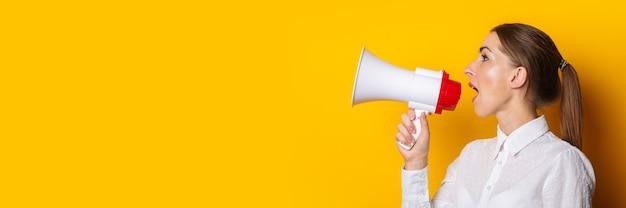 Jonge vrouw in een wit overhemd schreeuwt in een megafoon op een gele achtergrond. concept voor het inhuren, aanbieden, hulp gezocht. banier.