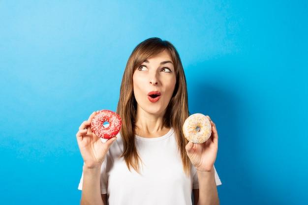 Jonge vrouw in een wit t-shirt houdt donuts geïsoleerd