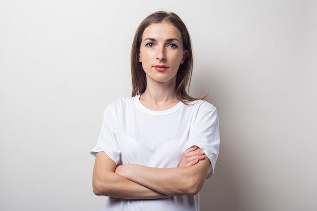 Jonge vrouw in een wit t-shirt met gekruiste armen op een lichte achtergrond.