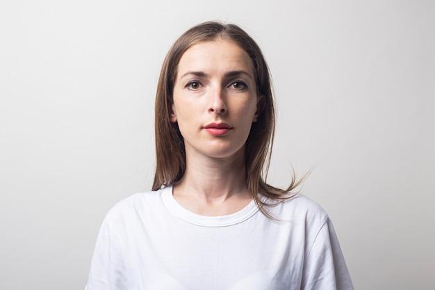 Jonge vrouw in een wit t-shirt op een lichte achtergrond.