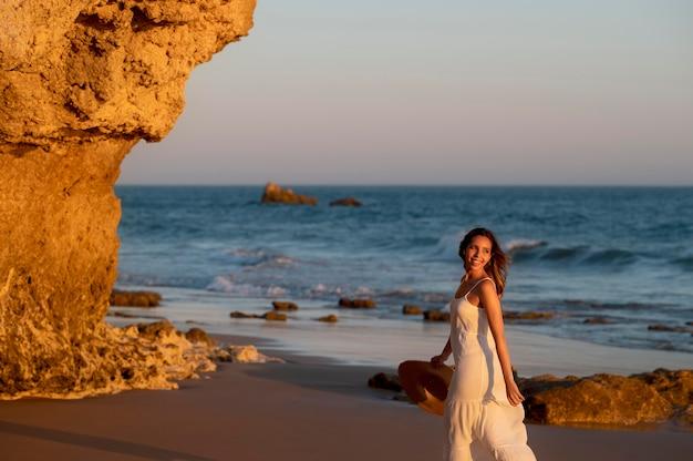 Jonge vrouw in een witte jurk aan zee