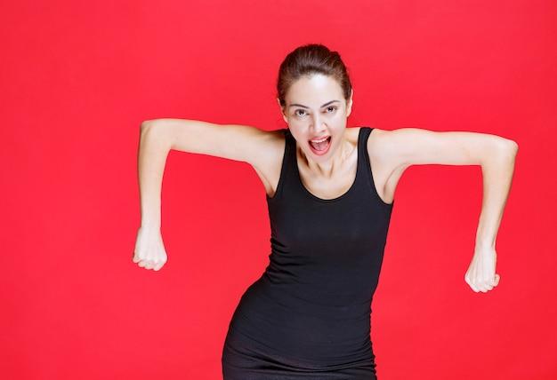 Jonge vrouw in een zwart hemd dat op de rode muur staat en haar armspieren laat zien