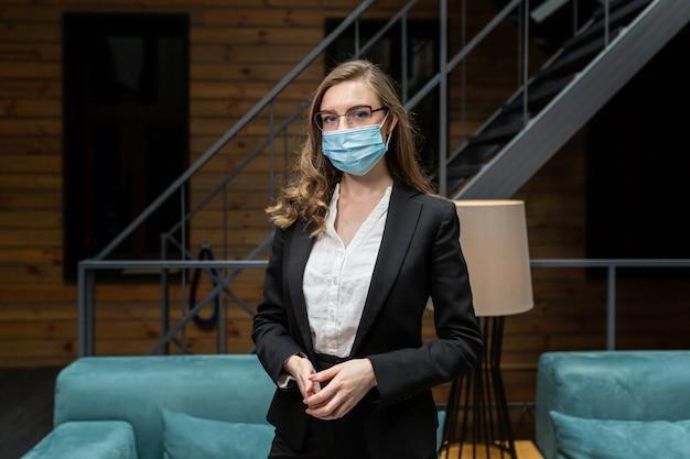 Jonge vrouw in een zwart pak kijkt naar de camera met een beschermend medisch masker op haar gezicht