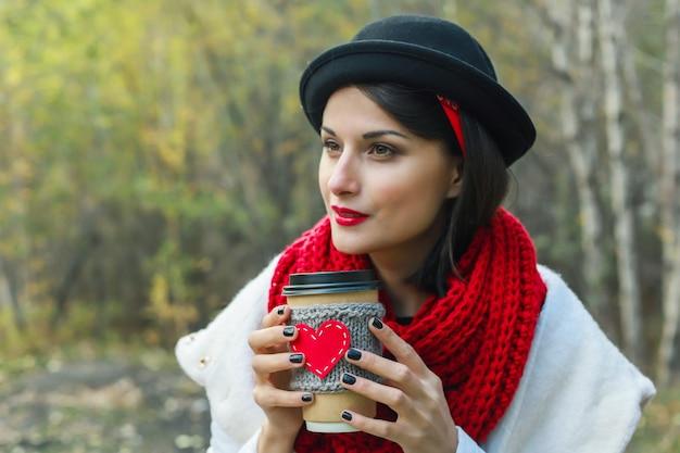 Jonge vrouw in een zwarte hoed drinkt koffie uit een gezellige kop op de natuur. een stralende glimlach en een goed humeur
