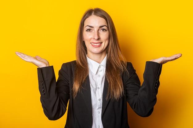 Jonge vrouw in een zwarte jas maakt een presentatie, houdt haar handpalmen op een gele.