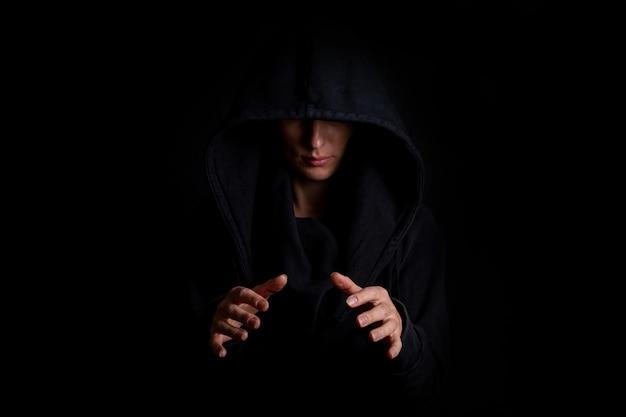 Jonge vrouw in een zwarte kap, handen met een onzichtbaar rond object op een zwarte achtergrond. Premium Foto