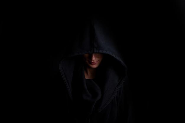 Jonge vrouw in een zwarte kap op een donkere zwarte achtergrond. Premium Foto