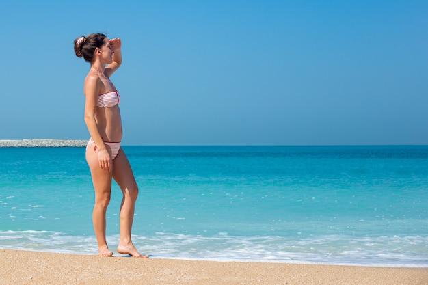 Jonge vrouw in een zwembroek kijkt in de verte naar de oceaan