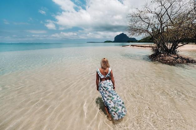 Jonge vrouw in een zwembroek ontspannen op een tropisch strand.