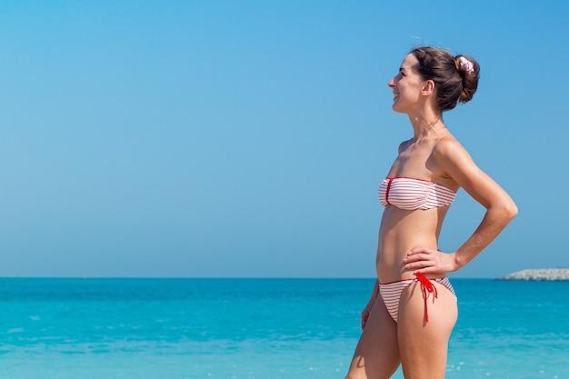 Jonge vrouw in een zwembroek tegen de muur van de zee en de blauwe lucht