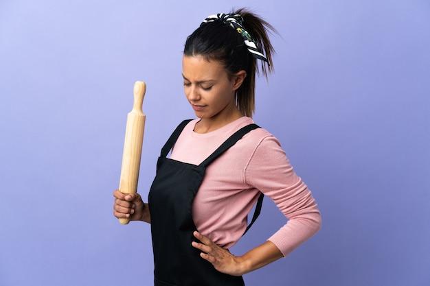 Jonge vrouw in eenvormig chef-kok die aan rugpijn lijdt omdat zij zich heeft ingespannen