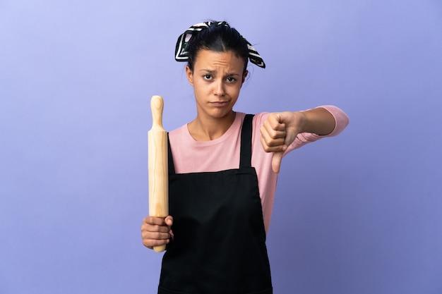Jonge vrouw in eenvormige chef-kok die duim met negatieve uitdrukking toont