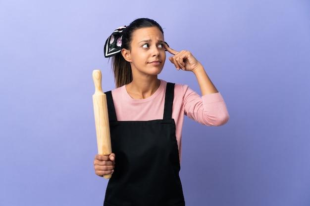 Jonge vrouw in eenvormige chef-kok die twijfels heeft en denkt