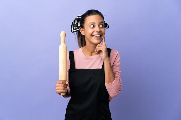 Jonge vrouw in eenvormige chef-kok een idee denken terwijl het opzoeken