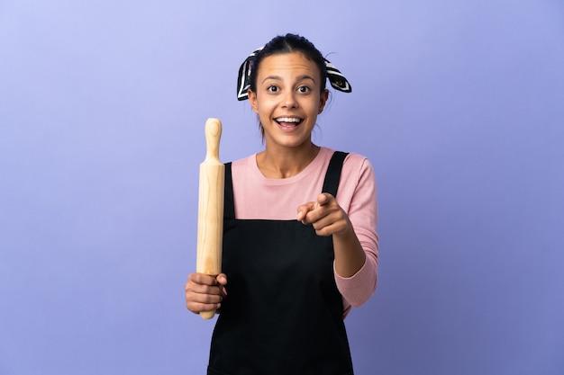 Jonge vrouw in eenvormige chef-kok verrast en wijst naar voren