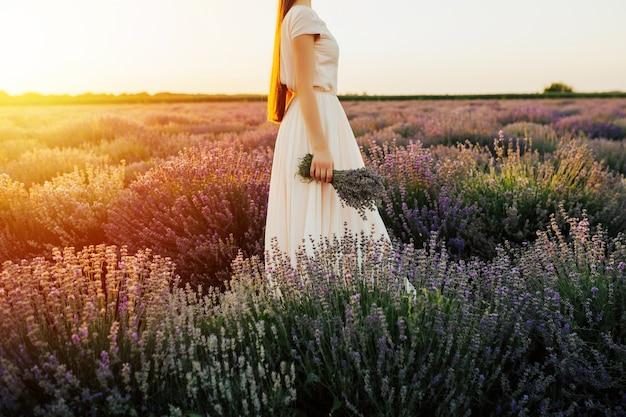 Jonge vrouw in elegante bleke roze jurk staande in de buurt van struiken van lavendel