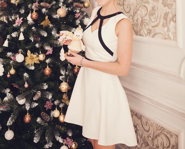 Jonge vrouw in elegante jurk zit naast kerstboom