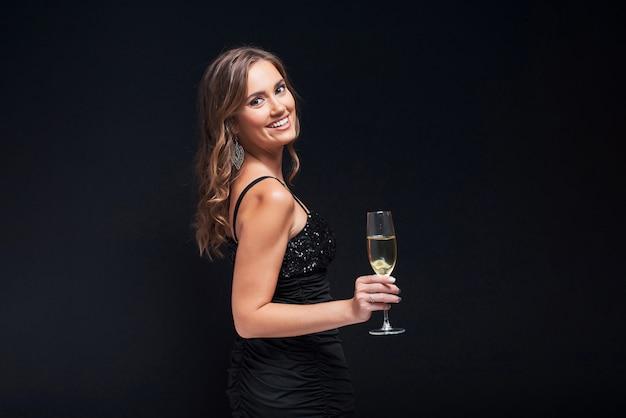 Jonge vrouw in elegante kleding die met glas champagne tegen zwarte blijft