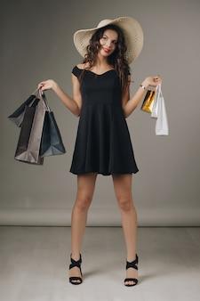 Jonge vrouw in elegante zwarte jurk en zomer hoed