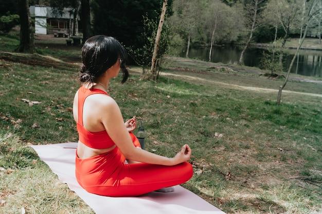 Jonge vrouw in fitness kleding doet yoga oefeningen op een yogamat in het park tijdens een zonnige dag