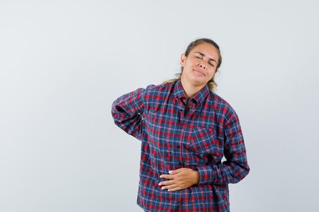 Jonge vrouw in gecontroleerd overhemd dat buikpijn heeft en uitgeput kijkt