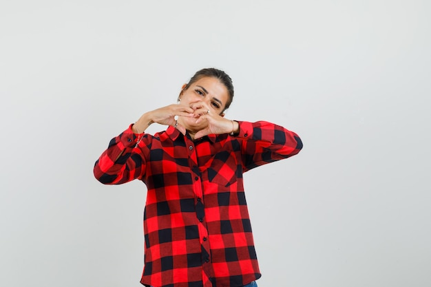 Jonge vrouw in gecontroleerd overhemd dat hartgebaar, vooraanzicht toont.