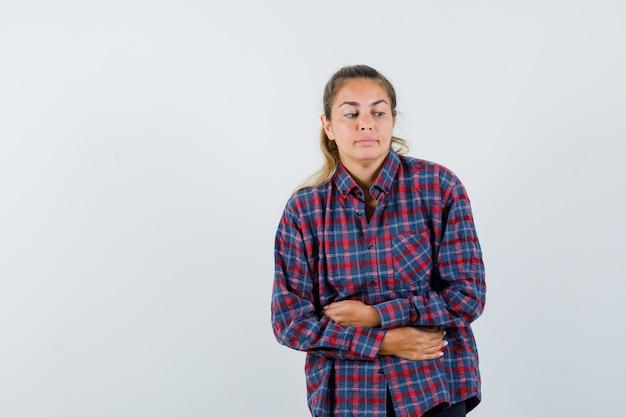 Jonge vrouw in gecontroleerd overhemd die buikpijn hebben en moe kijken