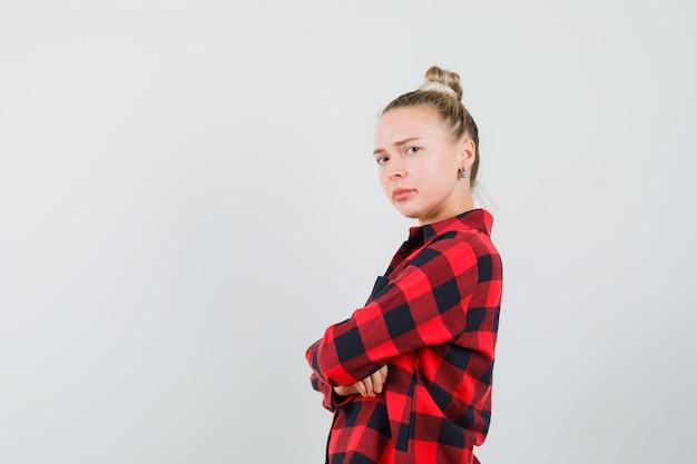 Jonge vrouw in gecontroleerd overhemd die zich met gekruiste wapens bevinden en boos kijken