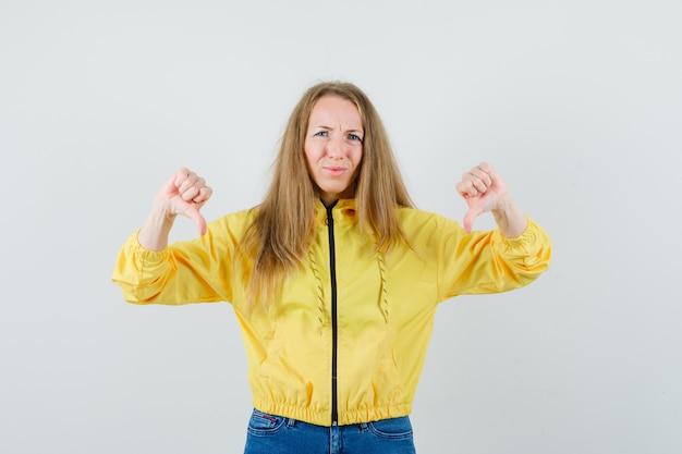 Jonge vrouw in geel bomberjack en blauwe jean die dubbele duimen naar beneden toont en ontevreden, vooraanzicht kijkt.