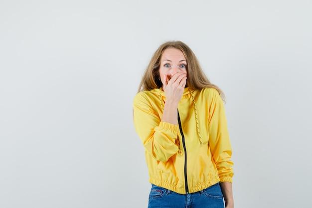 Jonge vrouw in geel bomberjack en blauwe jean die mond bedekken met hand en verbaasd, vooraanzicht kijken.